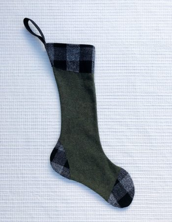 100% cotton flannel stocking with green body and black and gray check accents at cuff, toe and heel