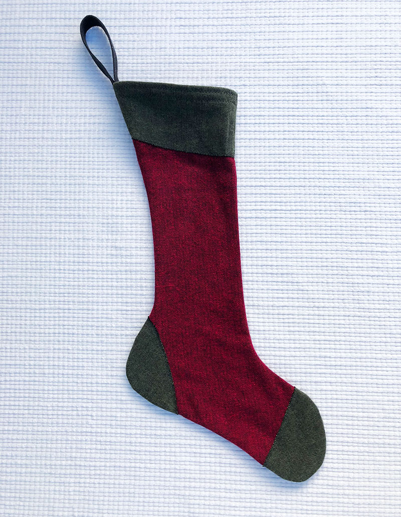 100% cotton flannel stocking with maroon body and green accents at cuff, toe and heel
