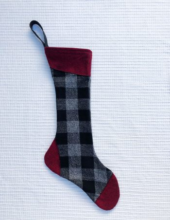 100% cotton flannel stocking with black and gray check body and maroon accents at cuff, toe and heel